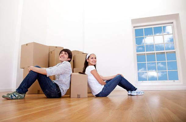 Couple with cardboard boxes moving to a new house